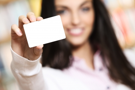 smiling young female showing a business card  -  copy space. Reklamní fotografie