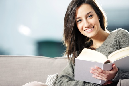 Portrait of a happy young woman lying on couch with book photo