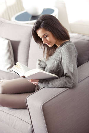 Portrait of a young woman lying on couch with book photo