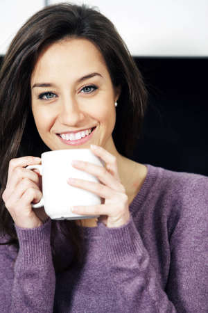Portrait of a cute young lady with a cup of coffee photo