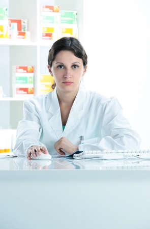 pharmacist sitting on her desk , looking at camera Stock Photo - 12578189