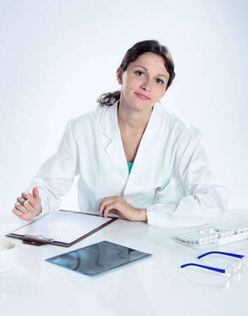 portrait of confident female doctor sitting on her desk  Stock Photo - 12578194
