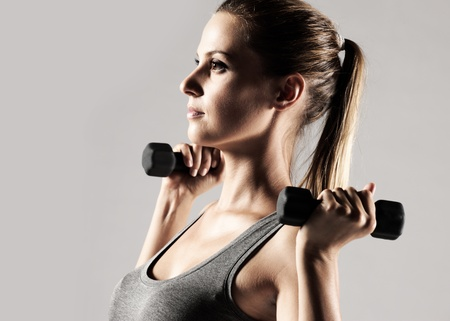 A beautiful woman raises with dumbbells Stock Photo - 12578306