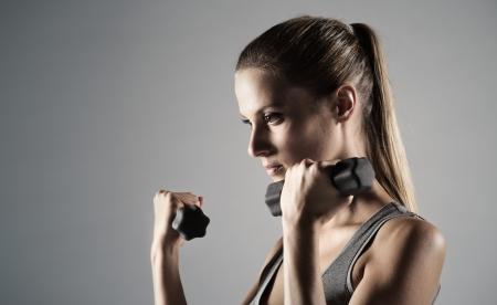 lifting: Een mooie vrouw roept met halters Stockfoto