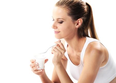 yogurt: Mujer joven comer yogur en el desayuno o merienda Foto de archivo