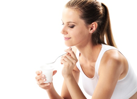 Young woman eating yogurt as breakfast or snack photo
