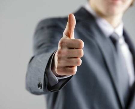 Close-up of a young businessman showing thumbs up. photo