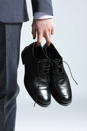 shoes fashion: businessman holding the shoes in hand, close up