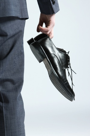 mens shoes: businessman holding the shoes in hand, close up