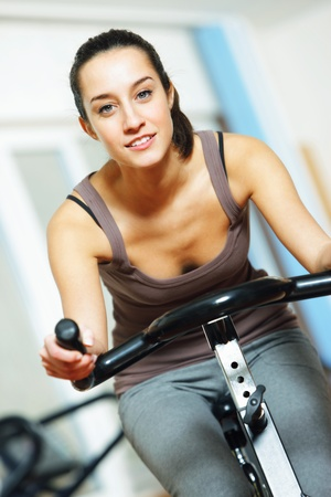 spinning: A young woman riding an exercise bike Stock Photo