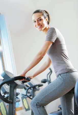 portrait of  young woman riding an exercise bike Stock Photo - 12842860