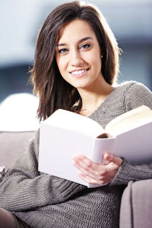 adult magazines: Portrait of a happy young woman lying on couch with book