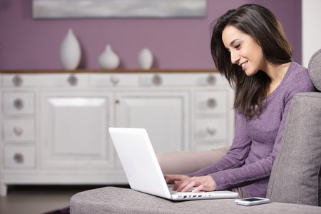 portrait of young woman on the sofa using laptop photo