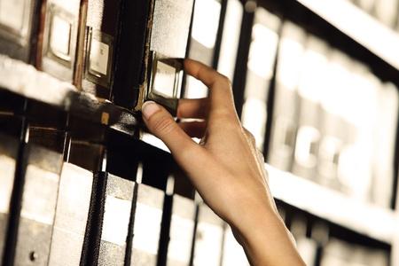 cassettiera: Ricerca negli archivi. Le mani degli studenti alla ricerca di un cabinet di riempimento.