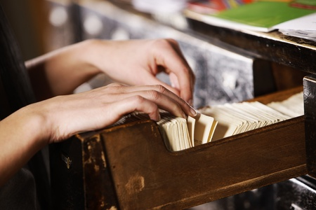 Searching in archives. Student hands searching from a filling cabinet.