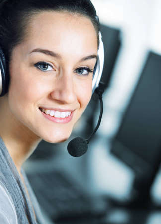 Cute business customer service woman smiling, computer on foreground Stock Photo - 12844279