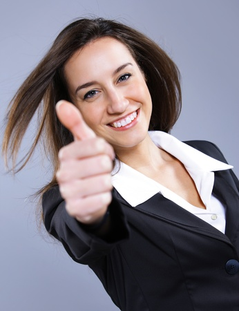 Businesswoman showing thumbs up sign photo