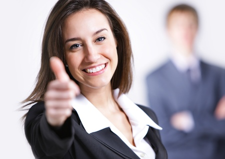 Businesswoman showing thumbs up sign, businessman on background Stock Photo - 12844194