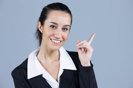 Young beautiful businesswoman pointing at copyspace photo