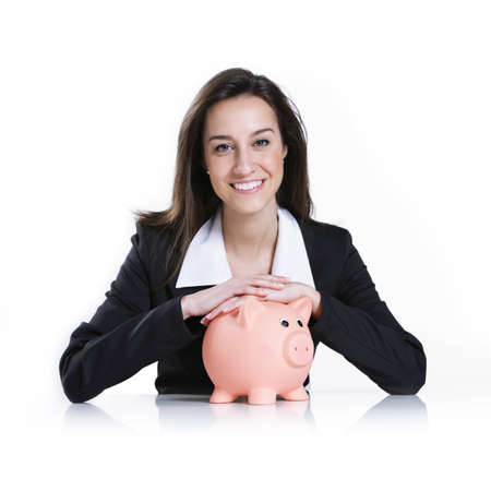 Close-up of young woman holding piggy bank against white background Stock Photo - 12844210