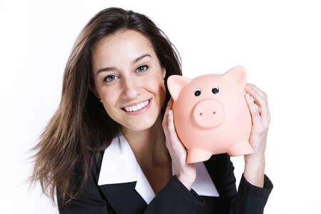 Close-up of young woman holding piggy bank against white background photo