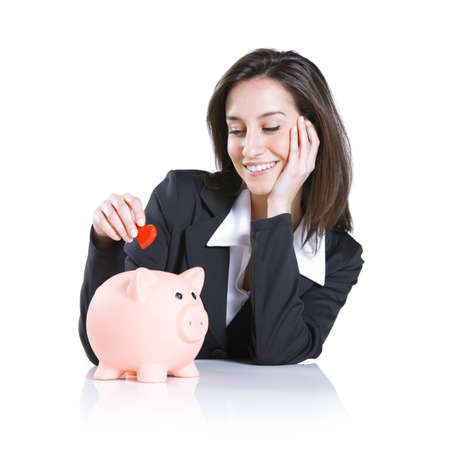 Close-up of young woman putting a red hearth  into a piggy bank, love concept Stock Photo - 12844225