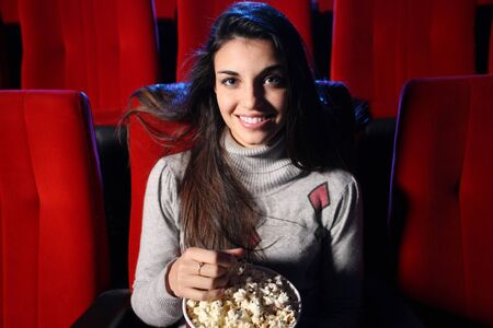 a pretty young woman sitting in an empty theater, she eats popcorn and smiles Stock Photo - 12899790