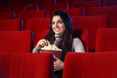 funny movie: portrait of a pretty girl in an empty theater, she eats popcorn and smiles photo