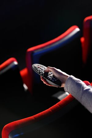 closeup of a hand holding a remote control TV, in the background you can see the red chairs in a movie theater. conceptual image photo