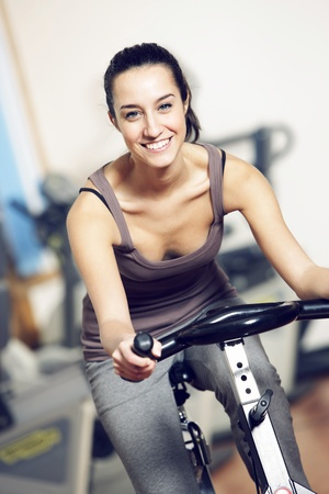 spin: A young woman riding an exercise bike Stock Photo