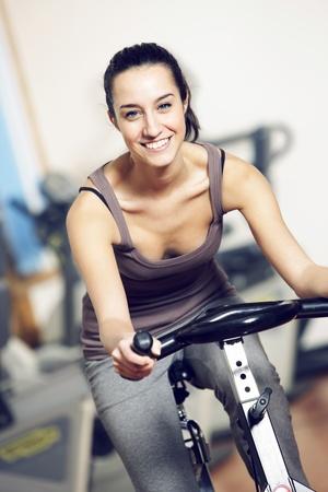 Une jeune femme chevauchant un vélo d'exercice