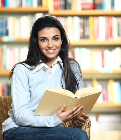 smiling female student with book in hands sitting in a chair in a bookstore - model looking at camera.  Stock Photo - 12834329