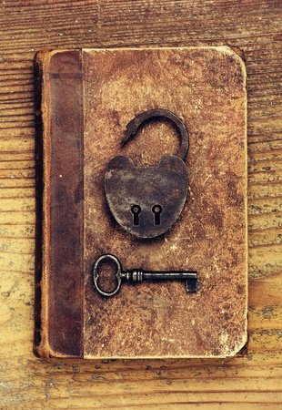 Antique Padlock with key on old book photo