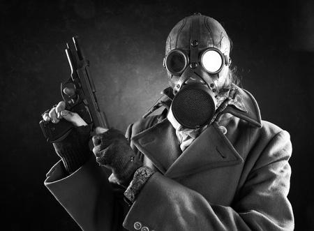 mascara de gas: grunge, el hombre del retrato en máscara de gas con una pistola