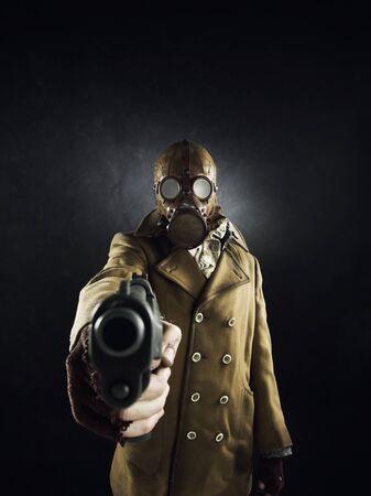 mascara de gas: el hombre del grunge retrato en máscara de gas apuntaba con una pistola Foto de archivo