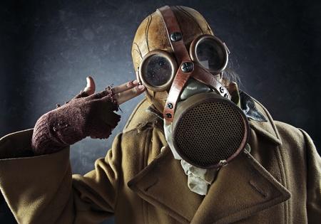 mascara de gas: el hombre del grunge retrato en máscara de gas que apunta la pistola a mano en su propia cabeza, el suicidio Foto de archivo