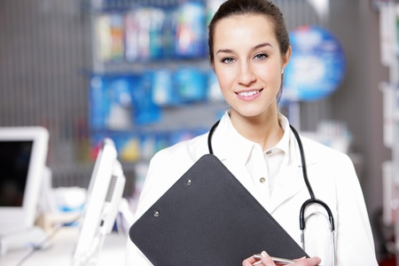 At pharmacy  A smiling young woman pharmacist wearing stethoscope  holding a medical chart Stock Photo - 12949224