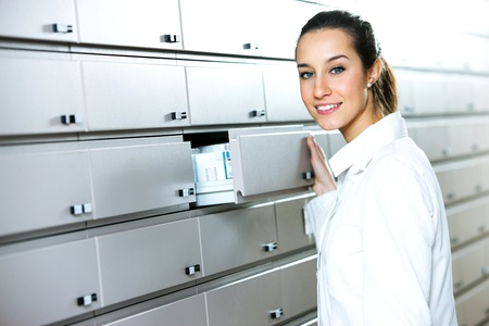 Young female pharmacist reaching for medicine  photo