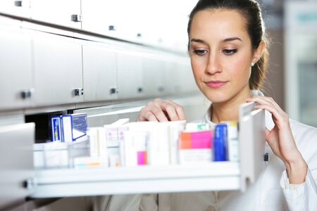 Young female pharmacist reaching for medicine  Stock Photo