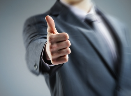 quality control: Close-up of a young businessman showing thumbs up. Stock Photo