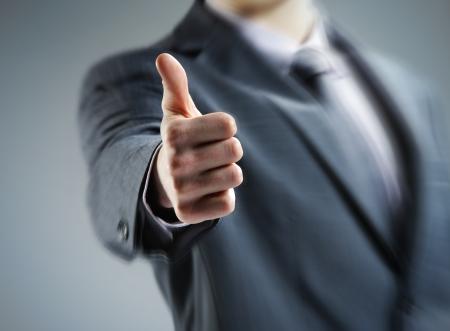 control de calidad: Primer plano de un joven hombre de negocios que muestran los pulgares para arriba.