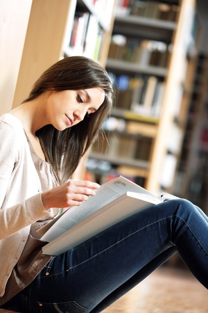 woman portrait: student reading a book at library photo