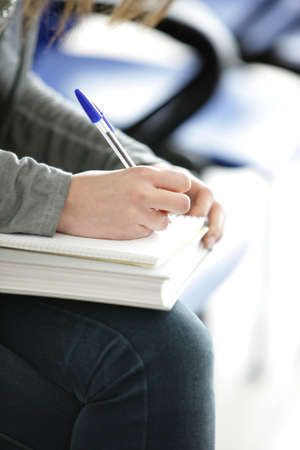 choose university: Young female is writing notes and planning her schedule