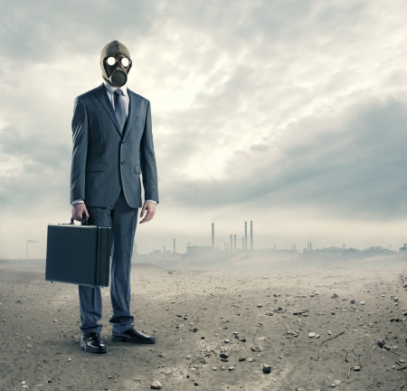 mascara gas: concepto de contaminación: retrato de hombre de negocios en una máscara de gas con la maleta Foto de archivo