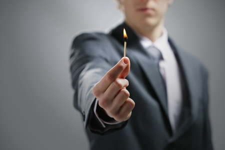 Business man hand holding a burning match
