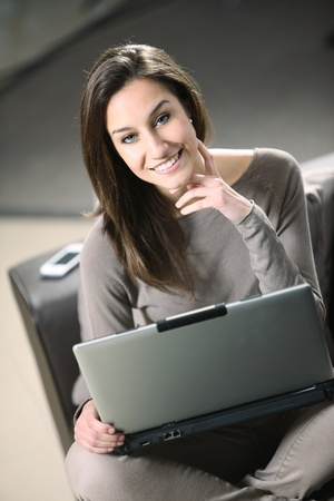 young woman at home, relaxing on a brown leather sofa with her laptop. photo