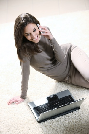 Smiling woman with mobile phone and laptop photo