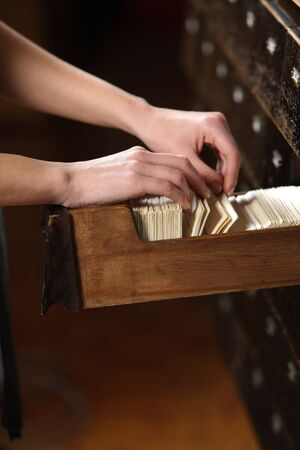 filing cabinet: Searching in archives. Student hands searching from a filling cabinet.