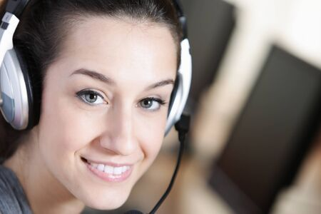 Cute business customer service woman smiling, computer on foreground photo