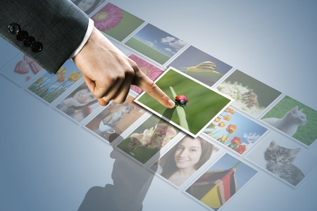 digitally concepts: futuristic display:man hand reaching images on the screen Stock Photo